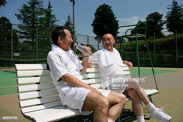 Two mature men relaxing at tennis court