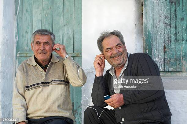 Two mature men sharing earphones and laughing.