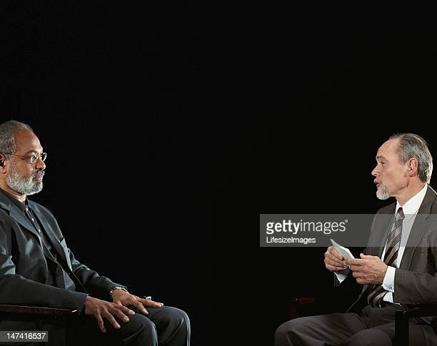 Two mature men sitting across from each other in interview