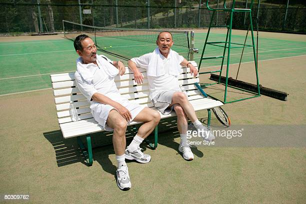 Two mature men sitting on bench in tennis court