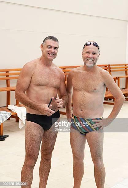 Two mature men standing in public swimming baths, smiling, portrait
