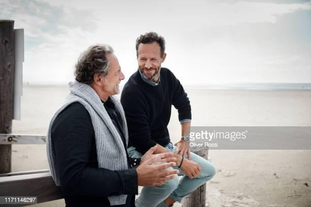 two mature men talking on boardwalk on the beach - travel stock-fotos und bilder