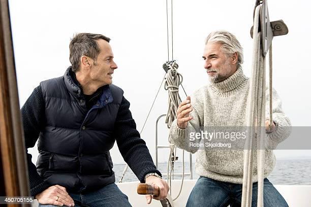Two mature men talking on sailingboat