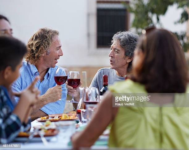 Two mature men toasting at dinner