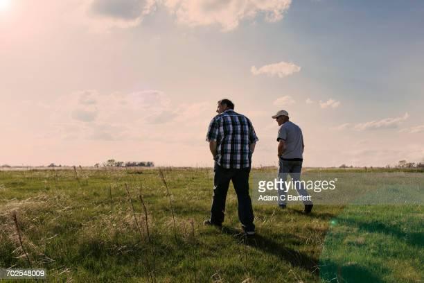 Two mature men walking in field landscape near Hastings Nebraska, USA