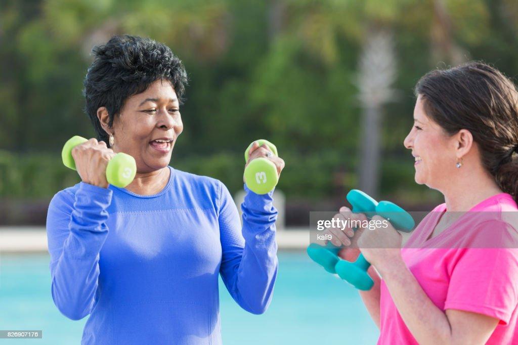 Two Mature Multiethnic Women Exercising Hand Weights Stock Photo