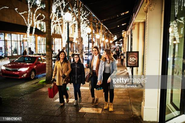 Two mature women and teenage daughters walking on sidewalk while shopping during holidays