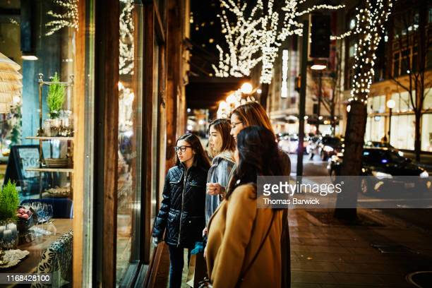 two mature women and teenage daughters window shopping during holidays - four people stock pictures, royalty-free photos & images