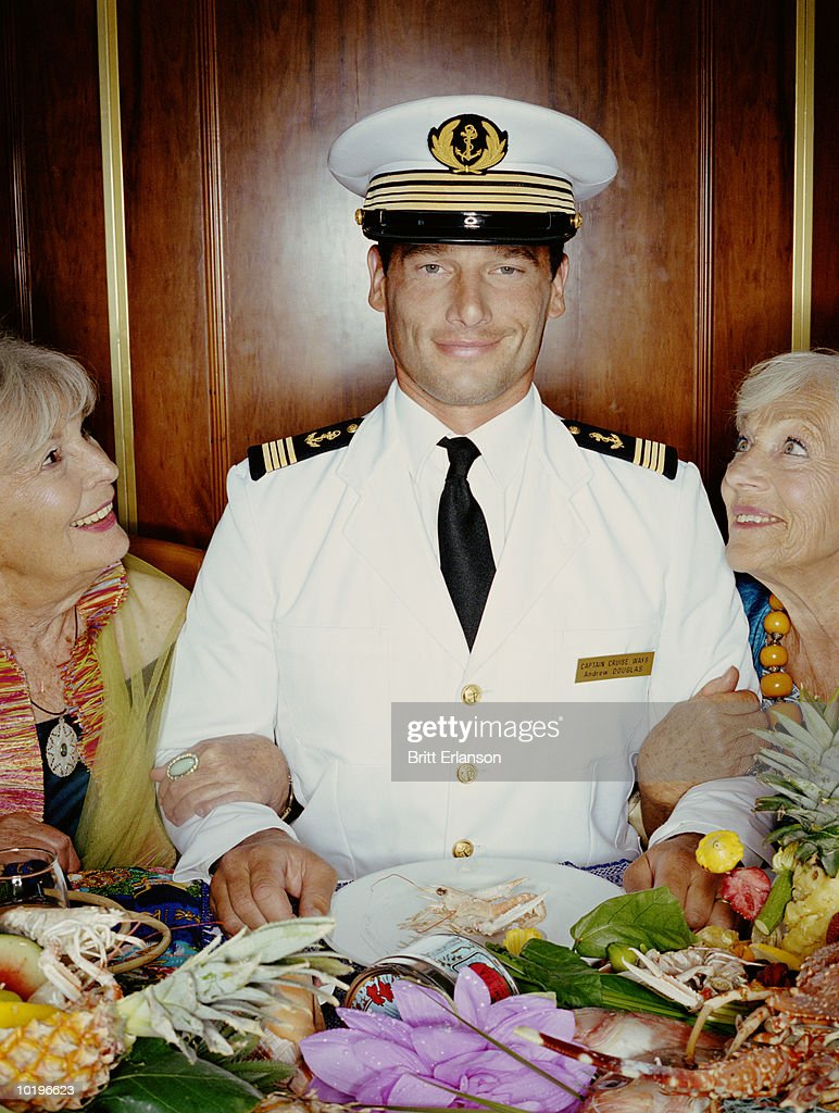 Two mature women arm in arm with captain at table, smiling, portrait : Stock Photo