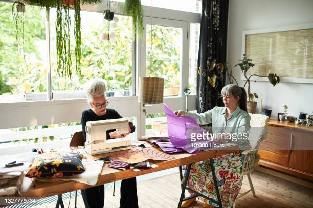 two mature women at home doing arts and crafts - greater london stock pictures, royalty-free photos & images