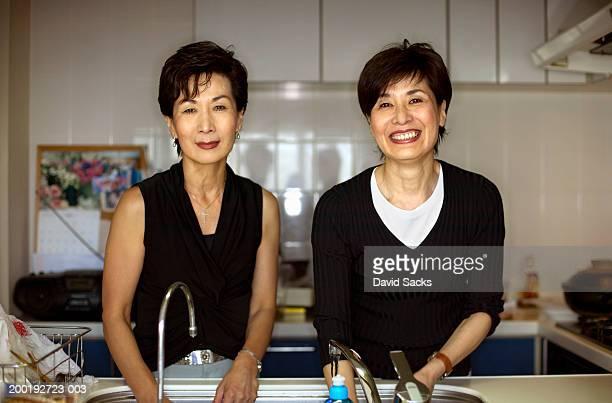 Two mature women at kitchen sink, portrait