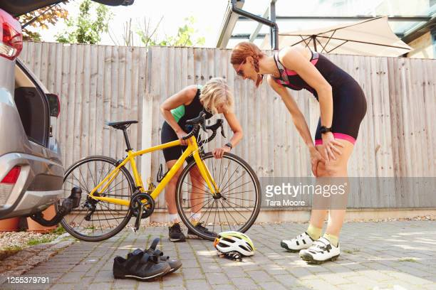 two mature women checking racing bicycle - adjusting stock pictures, royalty-free photos & images