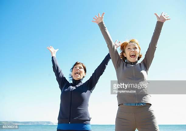 Two mature women cheering on beach