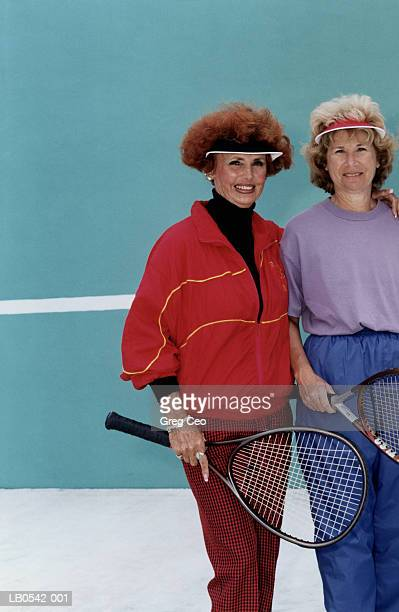 two mature women holding tennis racquets, portrait - trainingsanzug stock-fotos und bilder