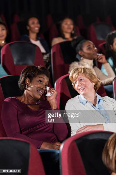 two mature women in movie theater, smiling and crying - girlfriends films stock pictures, royalty-free photos & images