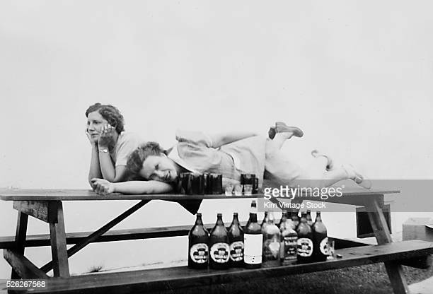 Two mature women laying on a picnic table seem to have had their fill after an afternoon of drinking