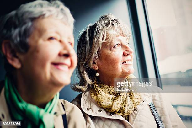 Two mature women looking at view from city train