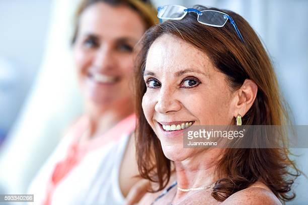 Two mature women posing smiling