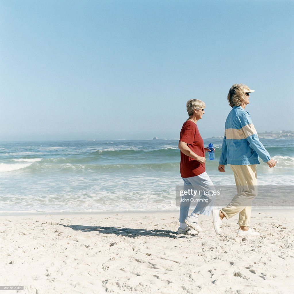 two mature women power walking on a sandy beach at the waters edge