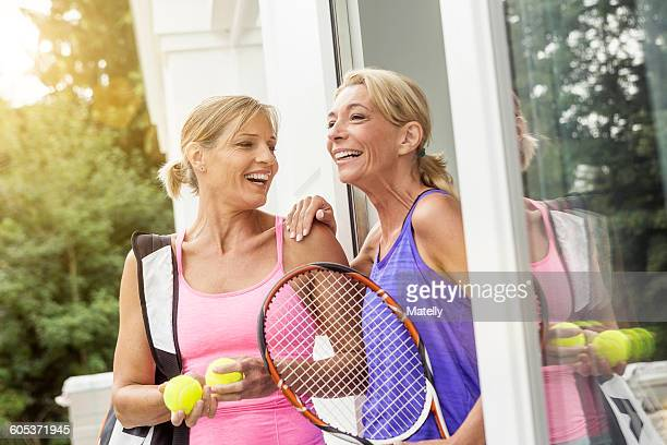 Two mature women preparing to play tennis at patio door