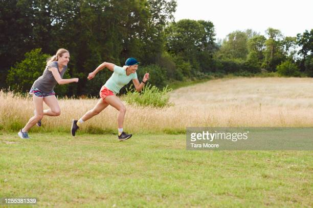 two mature women racing in park - sports race stock pictures, royalty-free photos & images