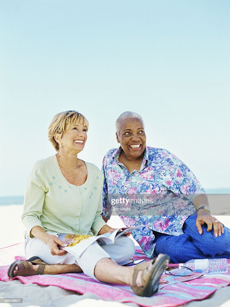 two mature women sitting on the beach stock photo | getty images