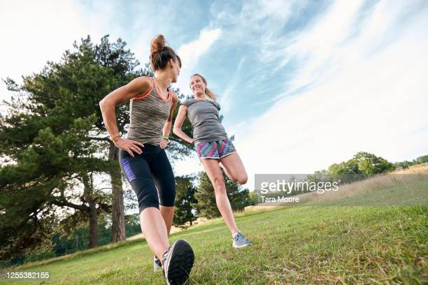 two mature women stretching in park - two people stock pictures, royalty-free photos & images