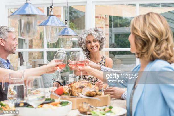 Two mature women toasting wine glasses with man in his 50s at dinner table