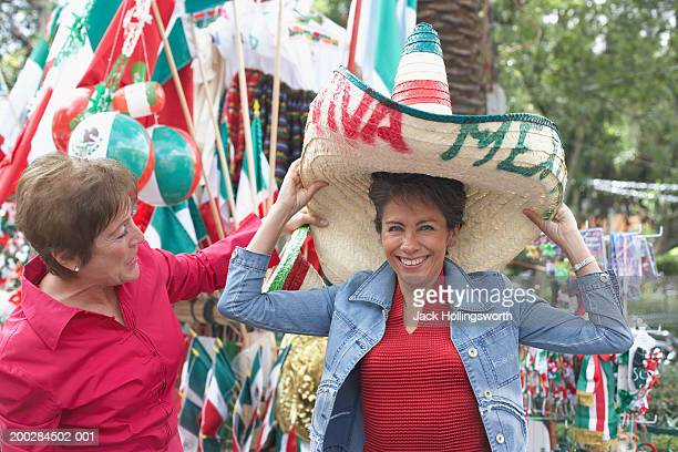 two mature women trying on sombrero's - mexican culture stock photos and pictures