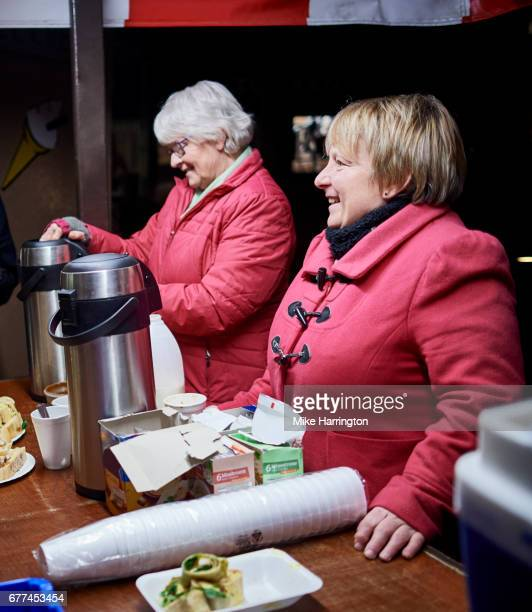 two mature women volunteering at local soup kitchen - altruism stock pictures, royalty-free photos & images