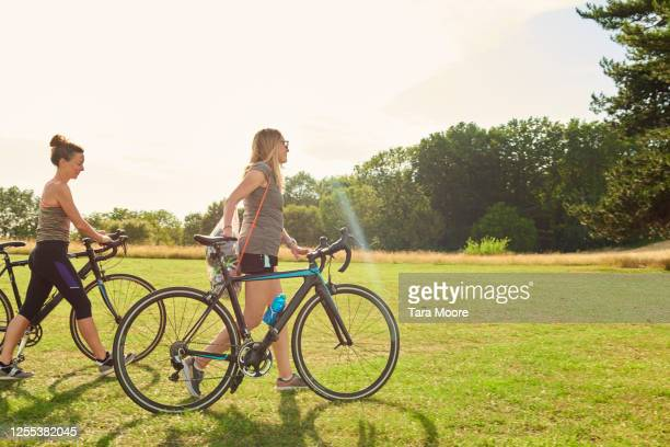 two mature women walking with bicycles in sunlight - riding stock pictures, royalty-free photos & images