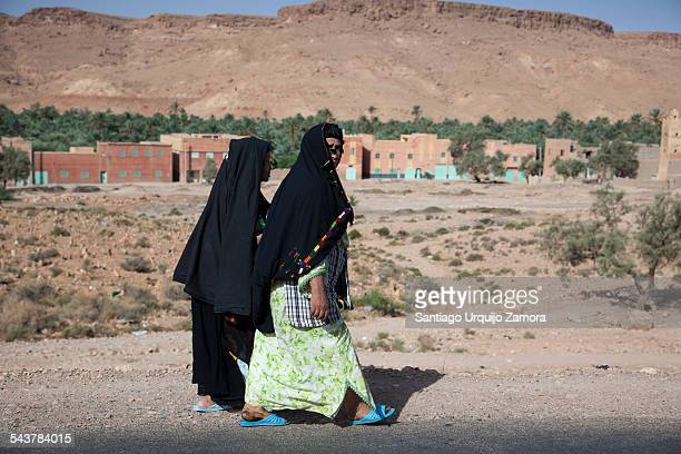 Two mature women wearing a black hijab walking alongside road with the village of Aoufouss on the background, Errachidia, Morocco