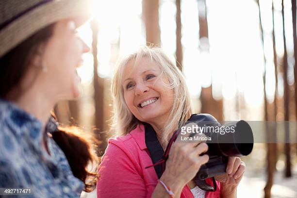 Two mature women with digital camera in forest
