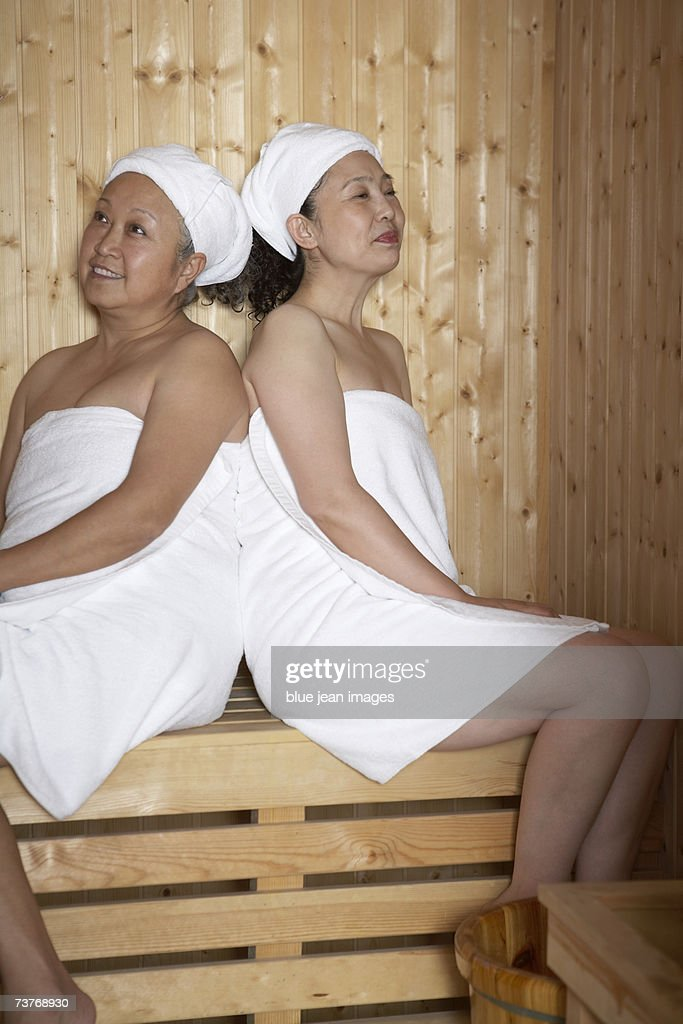 Two Mature Women Wrapped In Towels Smile As They Enjoy A Hot Sauna At The Spa