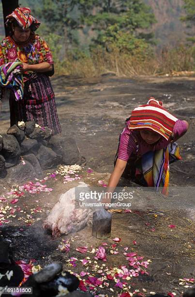 Two Mayan women make an offering to the diety Pascual Abaj in the outskirts of Chichicastanango Guatemala