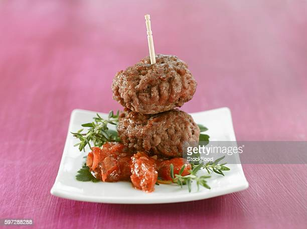 Two meatballs on tomato with herbs