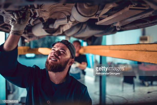 two mechanics checking underneath the car to find the problem - chassis stock pictures, royalty-free photos & images