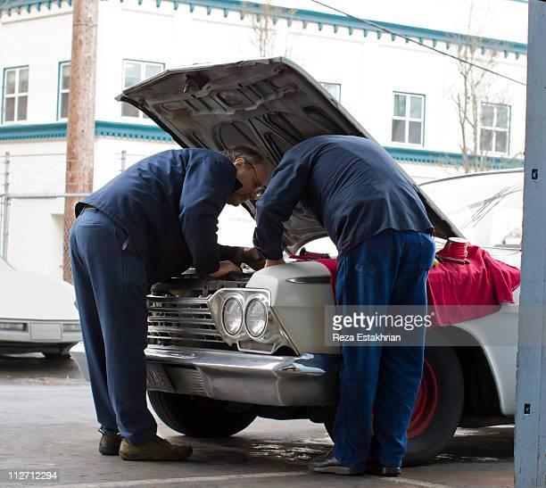 Two mechanics discuss auto repair