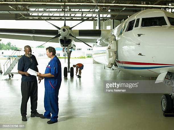 two mechanics discussing plans beside aero plane in hangar - hans neleman ストックフォトと画像