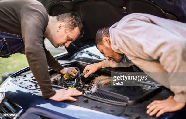 Two mechanics fixing a car.