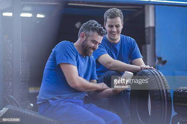 Two mechanics on a break looking at cell phone