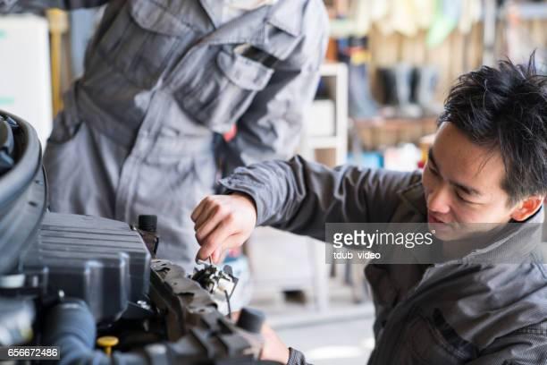 Deux mécaniciens travaillant ensemble dans un atelier de réparation automobile