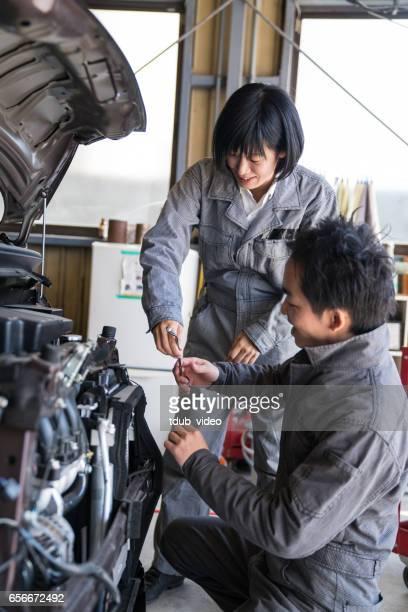 Zwei Mechaniker arbeiten zusammen in einer Kfz-Werkstatt