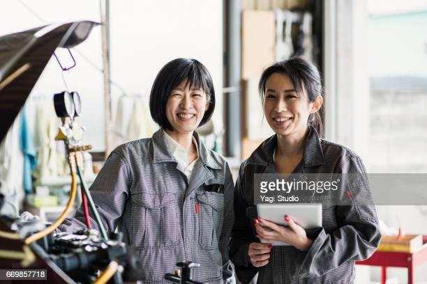 自動車修理工場で一緒に働く 2 つの力学 - オーバーオール ストックフォトと画像