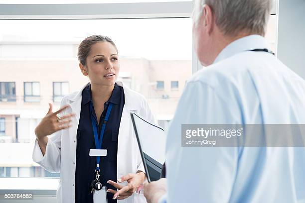 Two medical consultants talking in hospital, woman gesturing
