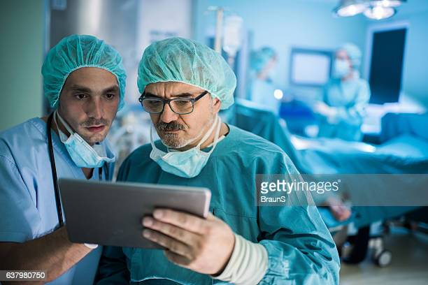 Two medical experts using palmtop in operating room.