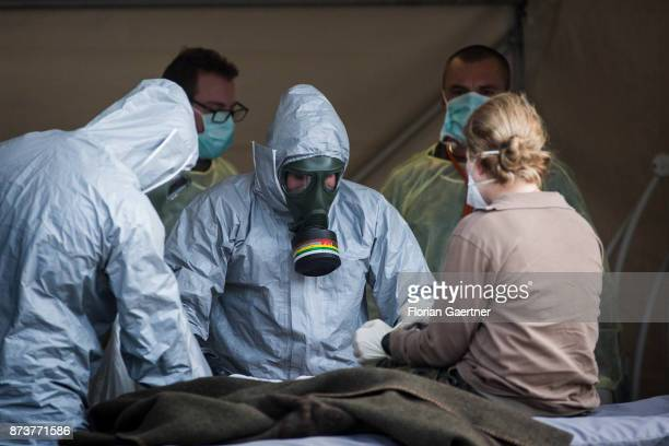 Two medical professionals wearing protective suits and gas masks treat a soldier Shot during an exercise of the land forces on October 13 2017 in...