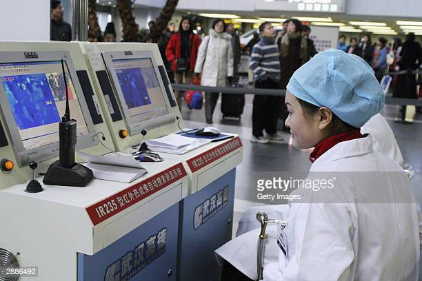Two medical workers monitor traveller's temperature at Beijing's capital airport January 21, 2004 as people struggle to head home to celebrate...