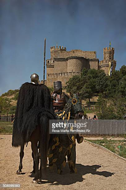 Two medieval knights on horseback get ready for the joust during annual Medieval Tournamet. The Manzanares el Real Castle as a background in summer...