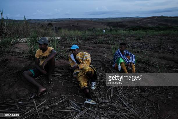 Two members of Maracatu and a spectator rest in a field of sugarcane after a presentation in the city of Nazaré da Mata in Northeast Brazil on...